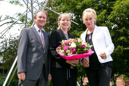 Ein Mann und zwei Frauen vor der Kamera. Die Frau in der Mitte hält einen Blumenstrauß in der Hand.