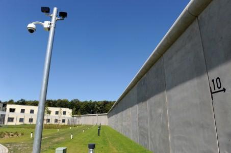 Auf dem Bild ist ein großes Gebäude vor einer hohen Mauer zu sehen.