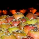 Ein Blech voller gezuckerter Äpfel vor einem Holzkohleofen.