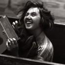 Ausschnitt des Ausstellungsplakats, die eine junge Frau mit einer Kamera in der Hand zeigt.
