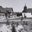 Historische Ansicht des Freilichtmuseums in Kommern, blick auf den See und die dahintergelegene Fachwerkhaussiedlung und Kirche.