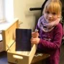 Ein blondes Mädchen blickt in die Kamera und zeigt einen Gegenstand, welchen es aus einer Holzbox hervorgeholt hat.