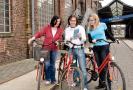 Drei Radfahrer. Der mittlere hält eine Radkarte in seinen Händen.