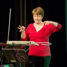 Eine Frau die auf der Bühne ein Theremin spielt.