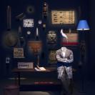 Ansicht eines Raumes mit verschiedenen Artefakten, darunter Masken, kleine Wandtextilien und Bilder. Im Vordergrund steht ein Tisch, an dem eine bekleidete Schaufensterfigur ohne Kopf anlehnt.