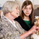Eine Ältere Dame zeigt einem jungen Mädchen eine Baumwollpflanze.