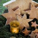 Ein brennendes Teelicht im leuchtet im Vordergrund, dahinter liegen Sterne aus Holz in unterschiedlichen größen, die auf Moos gebettet sind.
