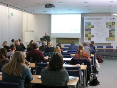 Ein Vortragender neben einer Leinwand auf der eine Präsentation gezeigt wird. Mehrere Zuhörende sind von hinten zu sehen.