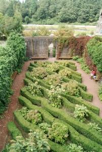 Von einer Mauer umfasster Bereich eines Parks. In der Mitte befinden sich wellenförmige Hecken. Im Hintergrund Parklandschaft. Innerhalb des eingegrenzten Bereichs sitzt ein Mann auf einer Bank.