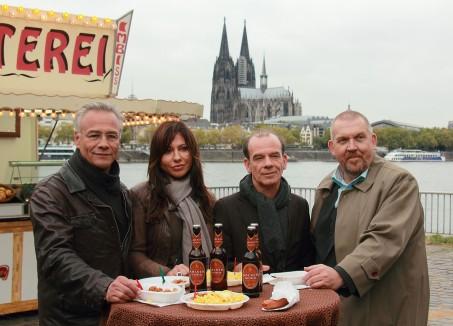 Vier Kommisare der Krimiserie Tatort stehen an einem Tisch neben einer Currywurstbude. Im Hintergund der Dom und der Rhein.