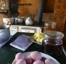 Einblick in eine alte Küche in einem Lehmhaus mit bunten Eiern und Töpfen