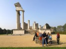 Foto: Menschen stehen vor den Überresten römischer Architektur.