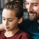 Ein Vater schaut mit seiner Tochter auf einen Bildschirm