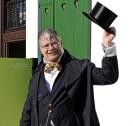 """Auf dem Foto ist ein Mann in Anzug und Gehstock zu sehen, welcher vor der St. Antony-Hütte steht. Er lüftet mit der linken Hand seinen Zylinder. Links von ihm ist das Schild der St. Antony-Hütte mit dem Untertitel """"Wiege der Ruhrindustrie"""" zu sehen."""