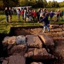 Auf dem Foto ist eine archäologische Ausgrabung zu sehen, bei welcher Baufragmente offengelegt wurden. Im Hintergrund sind mehrere Leute zu sehen, welche den Erläuterungen eines Fachmanns zu dem Ausgrabungsbefund lauschen.
