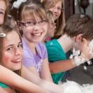 Eine Gruppe lachender Kinder, die Wolle in ihren Händen halten.
