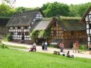 Foto: Blick auf historische Fachwerkgebäude, im Vordergrud eine grüne Wiese mit Menschen.