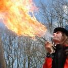 Ein Mann in einer roten Jacke spuckt Feuer.