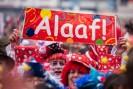 Foto: Kostümierte Menschenmenge, die ein Banner mit der Aufschrift