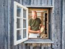 Foto: Blick in einen Raum durch ein geöffnetes Fenster. Dort backt ein Mann Brot.