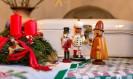 Foto: Rote Kerze inmitten von Tannengrün und Holzfiguren