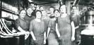 Foto: eine Schwarz-Weiss Fotografie, die mehrere Arbeiterinnen in der Baumwollspinnerei zeigt.