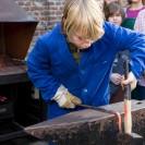 Ein Junge mit blonden Haaren schmiedet ein Stück Stahl. Andere Kinder und der Schmied schauen ihm dabei zu.